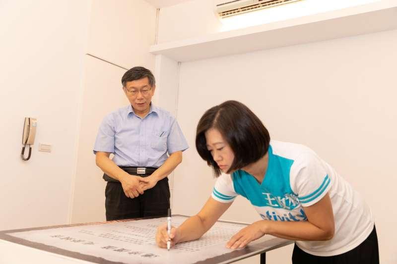 台北市長柯文哲跳脫「身份政治」的框限,得以超越藍綠。圖為國民黨中央委員王致雅簽署「柯P認同卡)。(柯文哲辦公室提供)