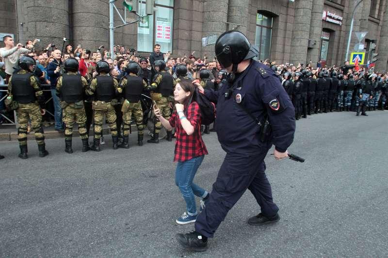 俄羅斯各地9日舉行示威活動,抗議政府的退休金改革計畫,女孩遭警方強硬驅離。(AP)