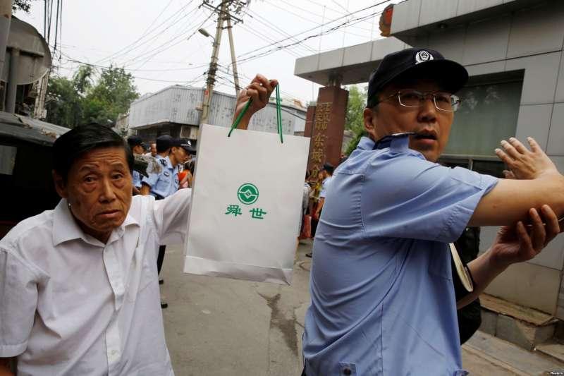 2018年8月27日,P2P投資計劃的受害人在北京東城區公安分局前面請願,一名男子拿著帶有P2P貸方徽標的袋子。(美國之音)