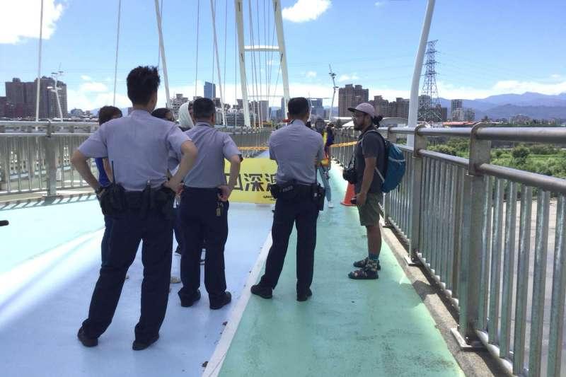 綠色和平組織約於新月橋以布條封路,新北市高灘地工程管理處通知警察人員協助取締中。(圖/新北市政府水利局提供)