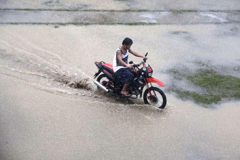 機車族注意,雨天積水深超過輪胎1/3就別涉水。(美聯社)