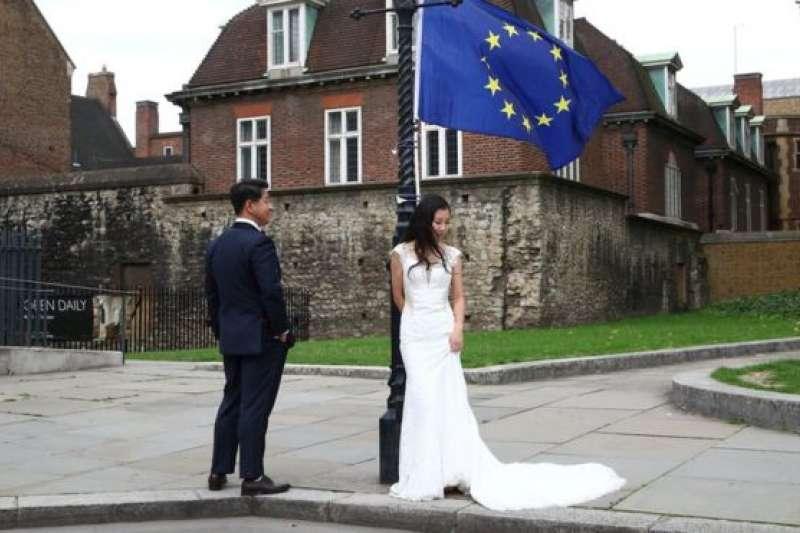 一對中國的新人在英國倫敦一處抗議脫歐者放置的歐盟旗幟下拍攝婚紗照。(BBC中文網)
