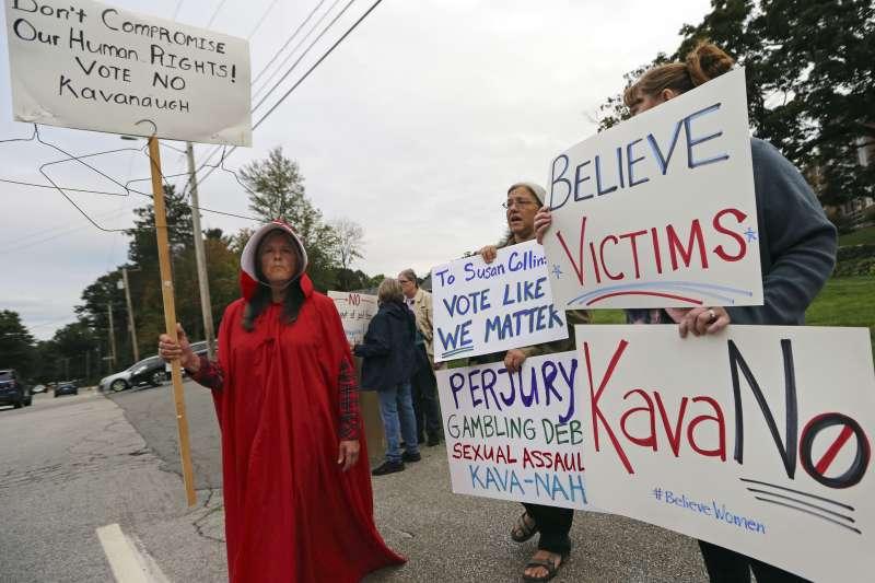 民眾拿著抗議標語,要求共和黨議員不要通過卡諾瓦任命案。(美聯社)