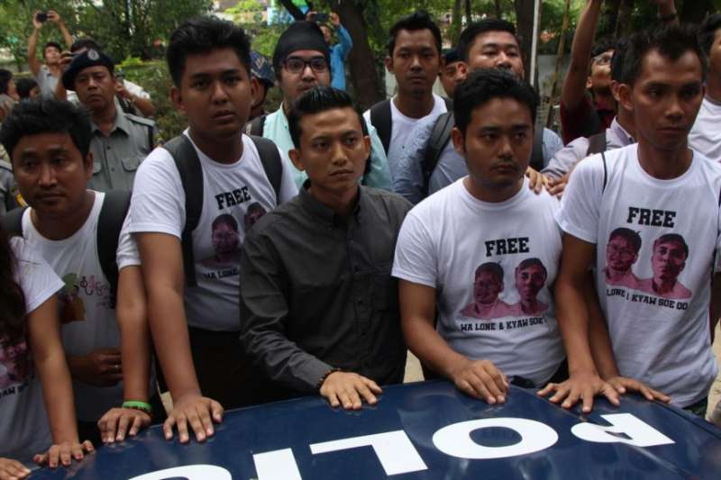 一群緬甸記者站在押送兩名《路透》記者的警車前(VOA)