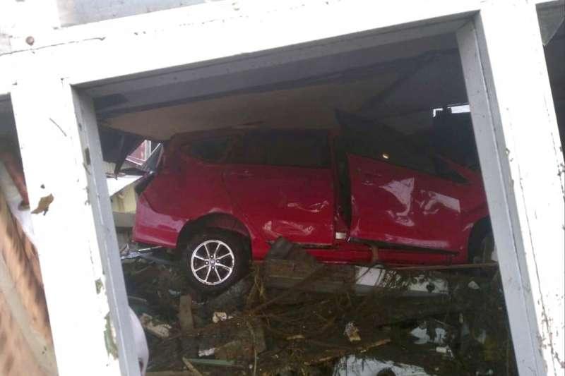 2018年9月28日,印尼蘇拉威西島發生規模7.5強震,車輛遭海嘯衝至建築物下方。(AP)