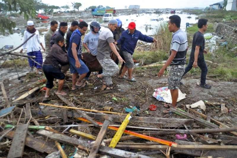 2018年9月28日,印尼蘇拉威西島發生規模7.5強震,民眾隔日運送罹難者遺體。(AP)
