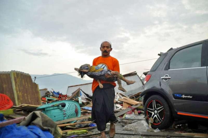 2018年9月28日,印尼蘇拉威西島發生規模7.5強震,引發3公尺海嘯,災區民眾抱著罹難孩童。(AP)