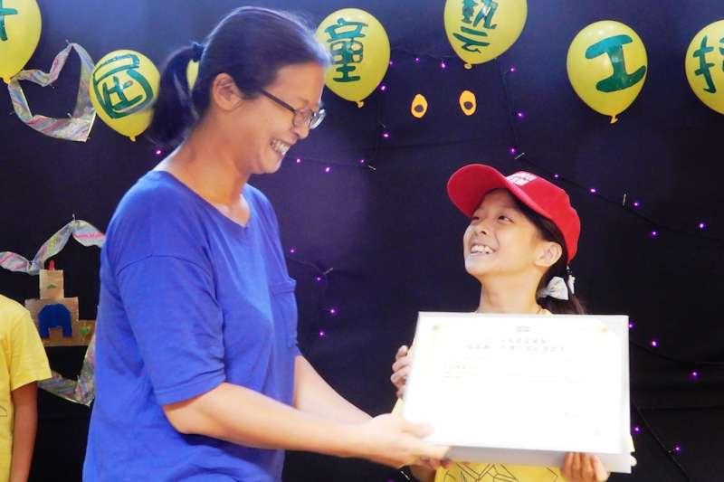 朱銘美術館邀請家長上台,親自頒授證書給取得證書成為「兒童藝工」的孩子,場面溫馨感人。(圖/新北市朱銘美術館提供)