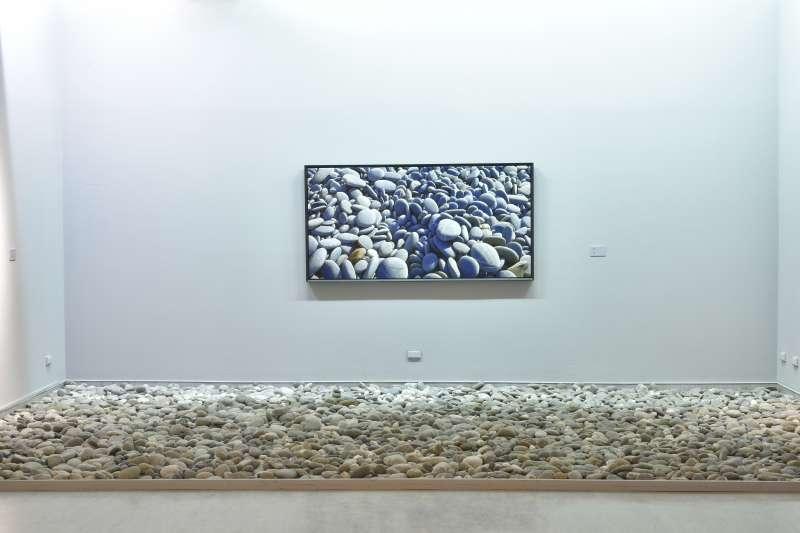 「石海之渡」個展悉心布置了一局人為畫作與自然元素之間、真假交融的意境。其中展示海畔巨石陣創作的房間底色亦為藍,讓人恍惚以為遁入了天地之間。(作者提供)