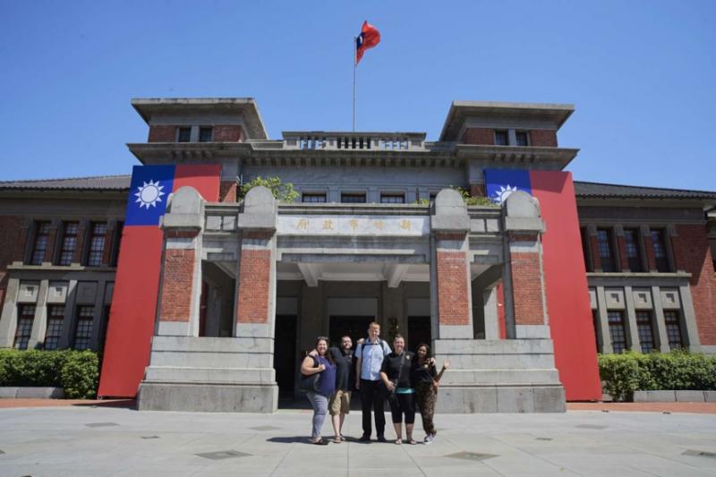 新竹州廳在正門左右兩側立面牆懸掛起2幅巨型長版國旗,不僅吸引行經市府前用的路人駐足,更有來自法國、加拿大、南非等多位外籍朋友爭相合影留念。(圖/新竹市政府提供)