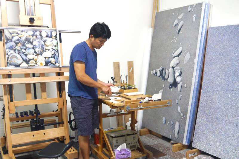 周珠旺每日幾乎只來回家中與畫室,之前所繪之石也多半取材自故鄉海邊的小薄片石。近期他則嘗試了紀錄其他地方的石頭,例如他後方畫作中的花蓮海岸石。(作者提供)