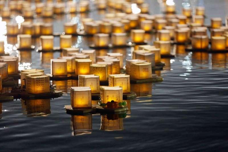 搖曳燭光映在水面上,「水燈節」讓新北市大臺北都會公園微風運河美不勝收。(圖/真如苑)