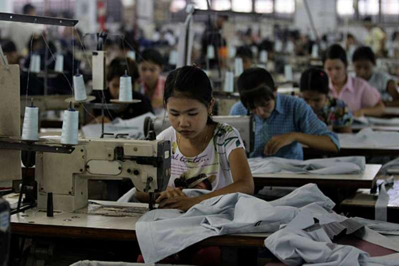 歐盟考慮對緬甸祭出經濟制裁,恐重創緬甸成衣紡織業。圖為2012年緬甸工人在仰光工廠縫製衣服。(AP)
