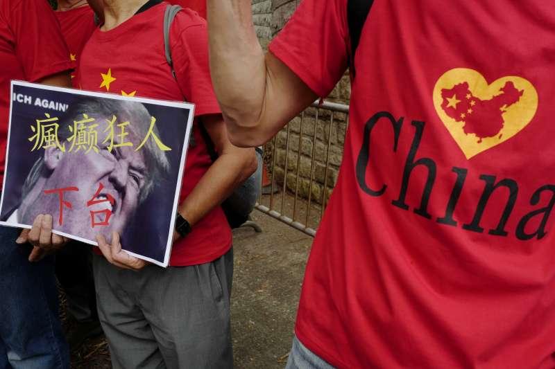 2018年10月1日,香港親中民眾高舉「瘋癲狂人下台」標語,抗議川普對中國發動貿易戰。(美聯社)