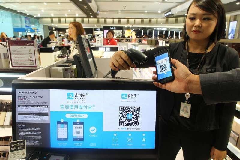 在南韓仁川國際機場免稅店,店員在演示支付寶付款方法(新華社)