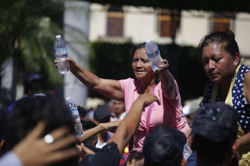 2018年10月22日,中美洲超過7000名移民抵達墨西哥南部,當地民眾向移民發送水等物資。(AP)