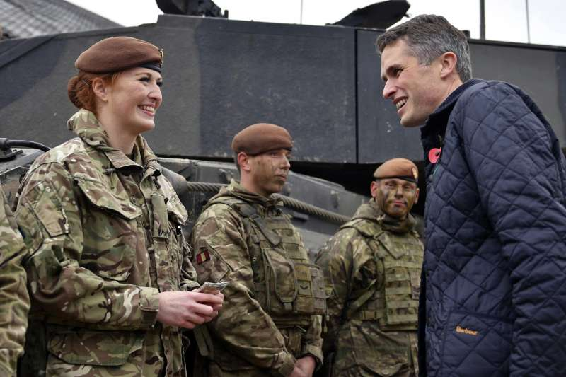 英國國防大臣威廉森(左)接見英國海軍女軍官。威廉森宣布,將全面取消女性從軍所擔任的職務限制,未來英國女性可以在受訓後加入空降特勤隊、海軍陸戰隊等前線作戰單位。(美聯社)