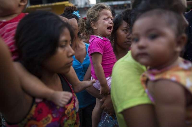 向美墨邊境前進的中美洲移民正在墨西哥等待物資發放,一個兩歲的小女娃不耐久候,在媽媽懷中哭了起來。(美聯社)
