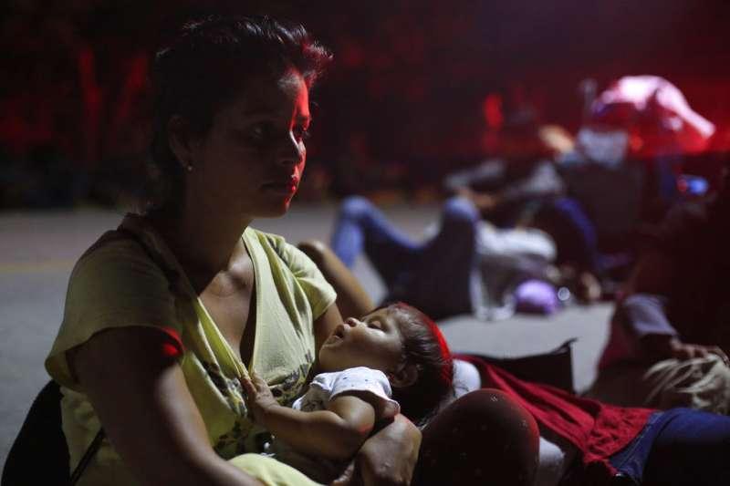 一位中美洲移民在墨西哥的公路邊哄睡孩子,希望能攔到便車送她們一程。(美聯社)