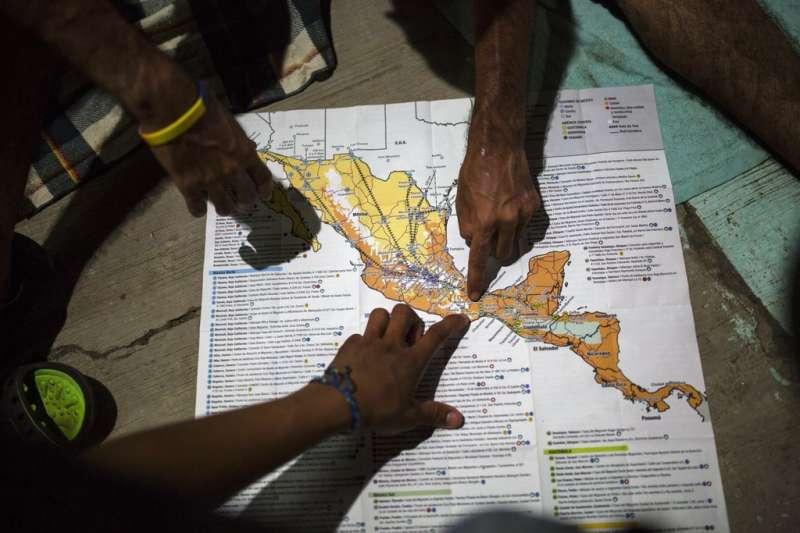 來自宏都拉斯的中美洲移民正在研究墨西哥地圖,討論前往美墨邊境的路線。(美聯社)