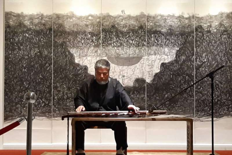 國父紀念館舉行《線之道,樊洲水墨世界巡展》,藝術家樊洲於開幕式彈奏清初明式黃花梨琴几,背後為其作品「乾坤」。(圖/寶吉祥藝術中心提供)
