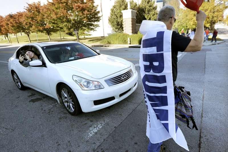 2018美國期中選舉11月6日登場,川普支持者穿著洗寫有川普名字的旗幟。(美聯社)