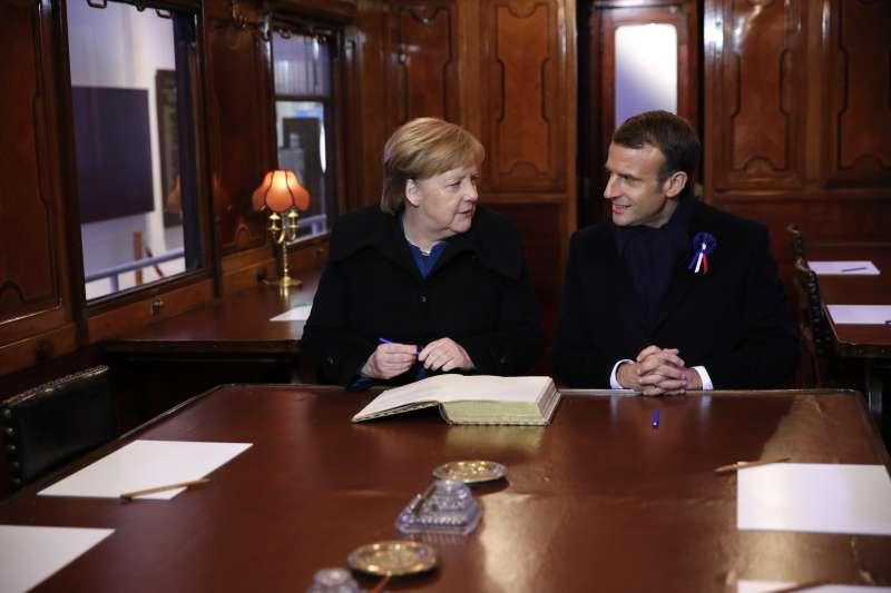 2018年11月10日,法國貢比涅「停戰博物館」,法國總統馬克宏與德國總理梅克爾來到100年前簽署一戰停戰協定的「2419D」火車車廂複製品,兩人在一本紀念專輯上簽名(美聯社)