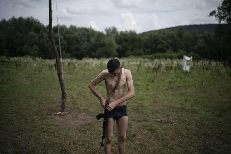 烏克蘭極右派團體舉辦青少年戰鬥營,學員要學會如何操作AK47步槍,將槍口對準敵人。(美聯社)