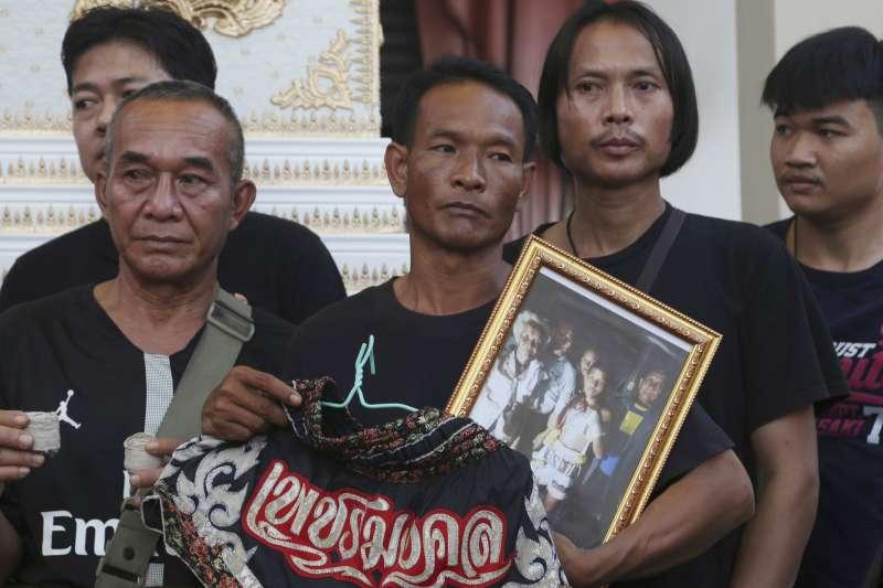 13歲的泰拳選手安努查因為腦溢血,在擂台上喪命,家人在喪禮中拿著他的遺照。(美聯社)