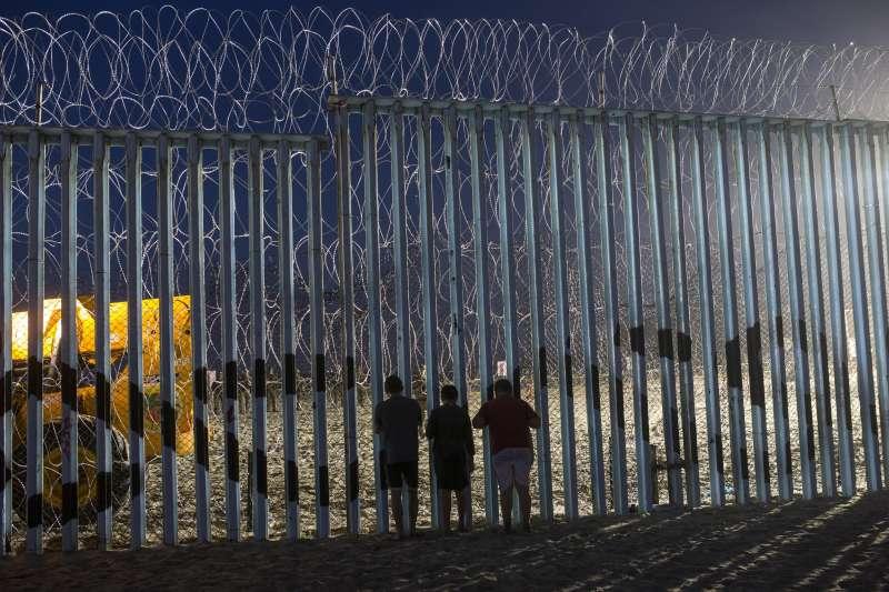 位於美墨邊境的高牆,布滿刺鐵網。(美聯社)