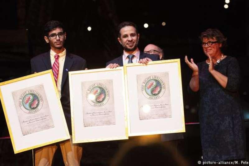 3位被監禁獲獎人的律師阿斯里(中)代替得主出席了頒獎儀式(DW)