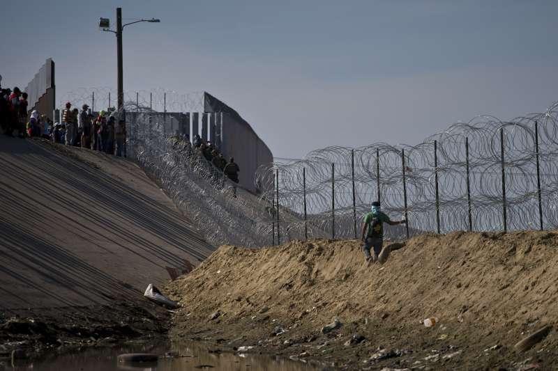 2018年11月25日,美墨邊境的中美洲移民試圖翻過圍欄,進入美國尋求庇護。(美聯社)