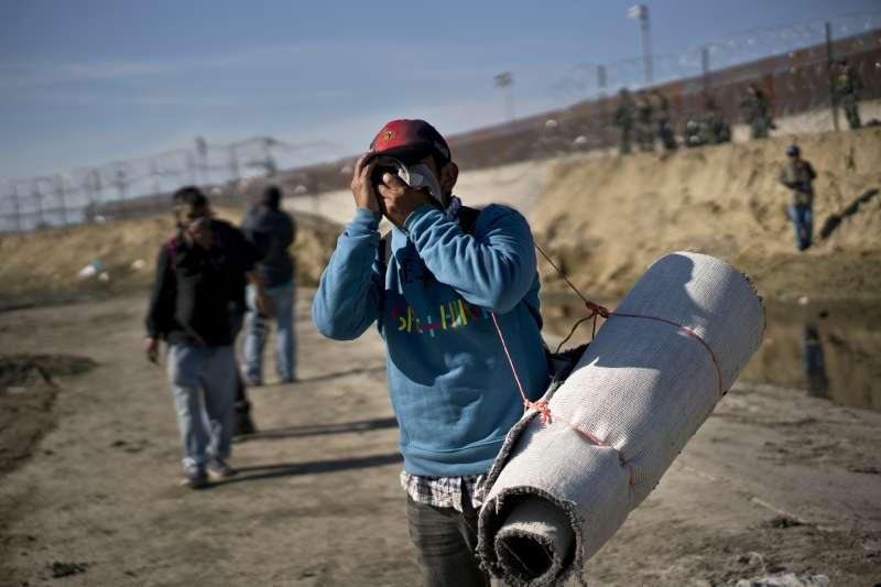 2018年11月25日,美墨邊境的中美洲移民為了躲避催淚瓦斯而四處逃竄。(美聯社)