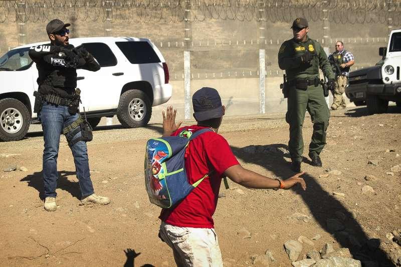 2018年11月25日,美墨邊境的中美洲移民試圖衝破防線,進入美國尋求庇護。(美聯社)