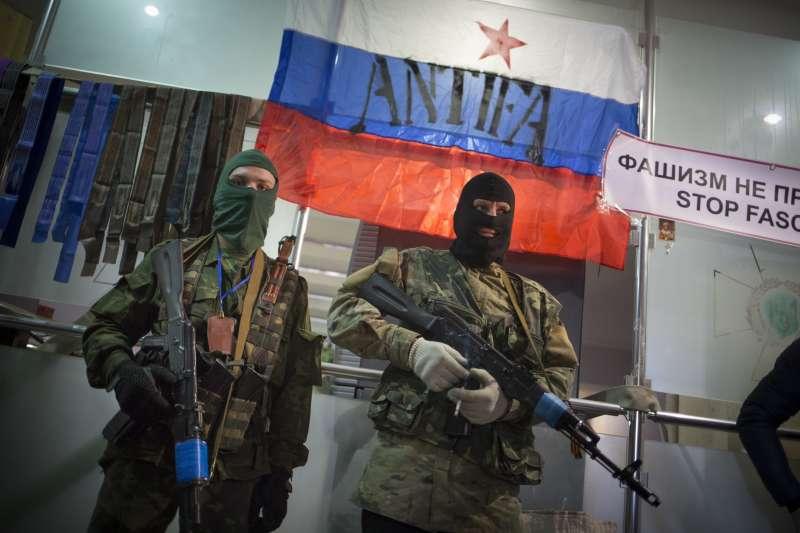 戴著面具的親俄羅斯槍手駐守在烏克蘭安全局區域辦事處的入口處,並在門上掛了俄羅斯國旗。(美聯社)