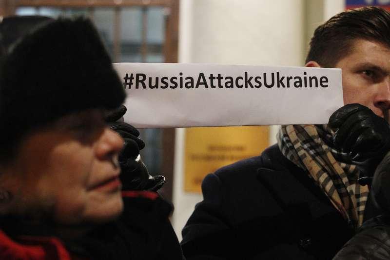 俄羅斯華沙,示威者舉著「俄螺絲攻擊烏克蘭」的標語,抗議俄國對烏克蘭發動攻擊。(美聯社)