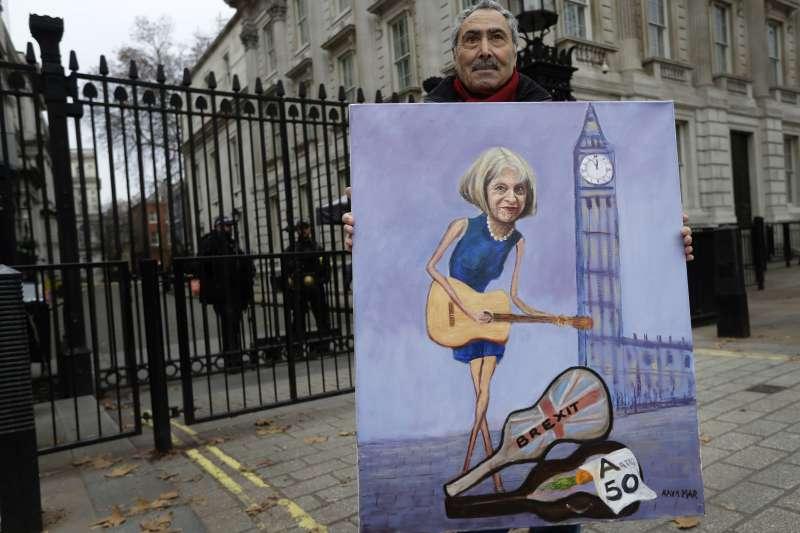 一名英國畫家拿著梅伊的畫像在英國國會前。(AP)