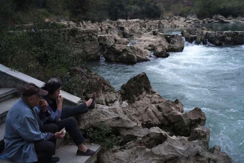 在廣西巴馬瑤族自治縣,一對老年夫妻在盤陽河邊靜坐。(新華社)