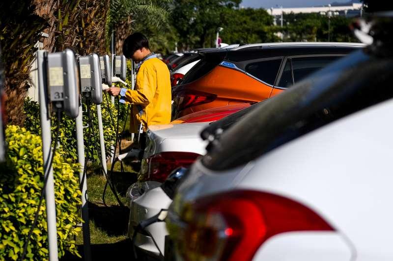 在位於深圳的比亞迪總部,一名工作人員為新能源汽車充電(新華社)