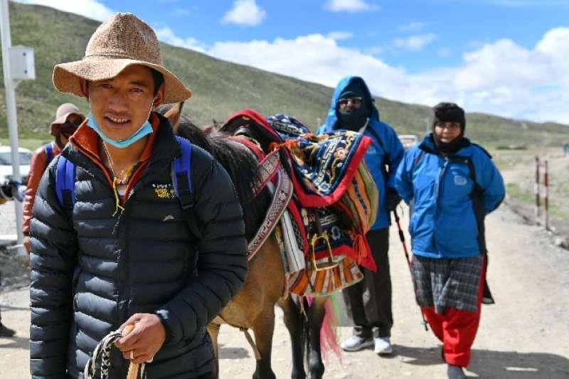 一名西藏阿里的農牧民為到岡仁波齊朝聖的印度香客牽馬駝運物資(新華社)