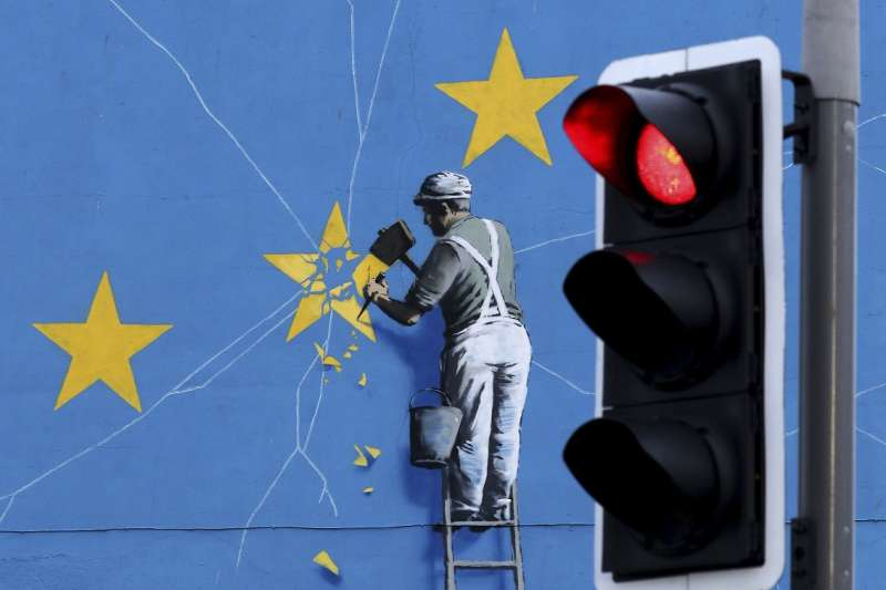 英國知名塗鴉藝術家班克西(Banksy)在英國東南部海港多佛繪製的「脫歐」壁畫,描繪一名男子逐漸敲下代表歐盟的旗幟(美聯社)