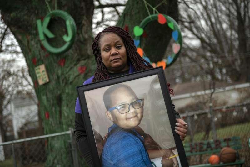 美國12歲小男孩克拉庫拉克打零工為病逝好友葛羅斯買下墓碑,圖為葛羅斯的母親手抱葛羅斯的照片。(AP)