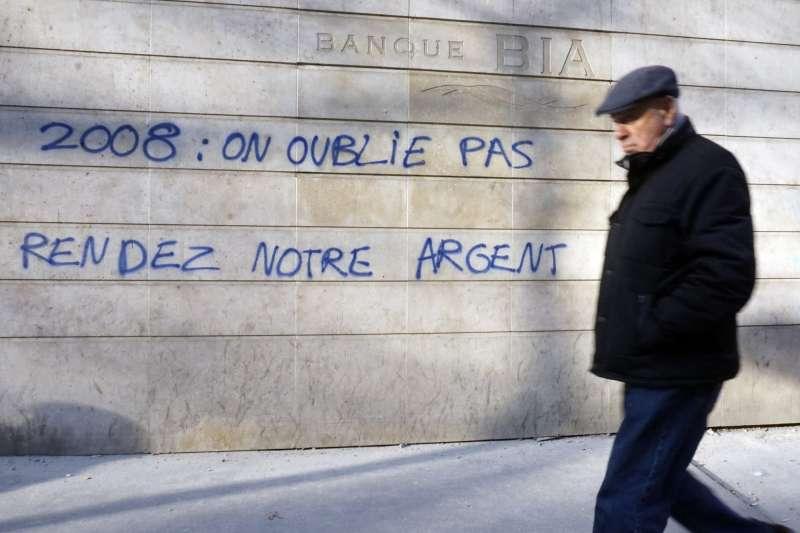 2013年12月13日,一名男子經過法國巴黎的一面牆,牆上用噴漆寫著「2008年:我們沒有忘記,把錢還給我們。」(美聯社)