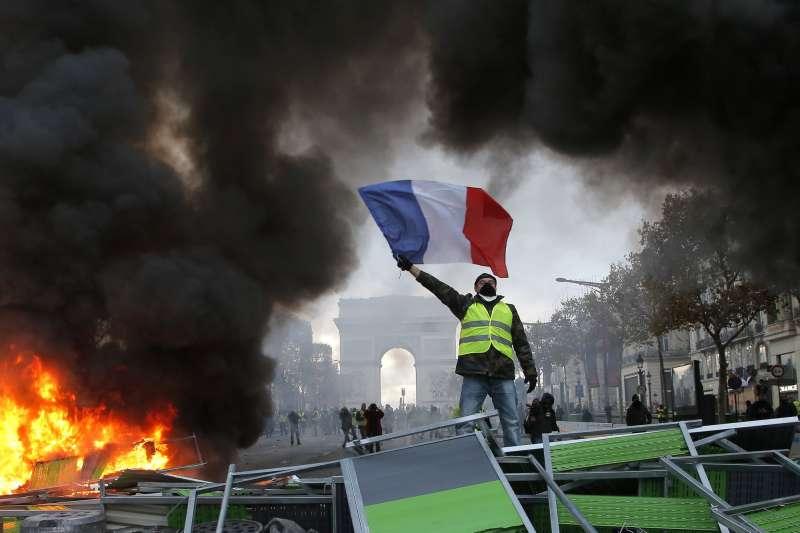2018年11月24日,穿著黃背心的抗議男子站在通往法國總統府艾麗榭宮前被焚燒的拒馬,高舉著法國國旗。(美聯社)