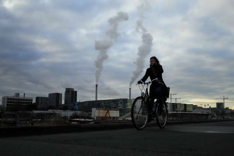 2018年12月4日,巴黎街頭一位女子騎著腳踏車經過排放黑煙的工廠。(AP)
