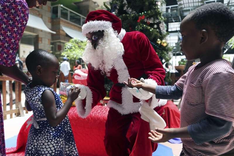 南部非洲國家辛巴威慶祝耶誕,耶誕老人發送糖果給孩童(AP)