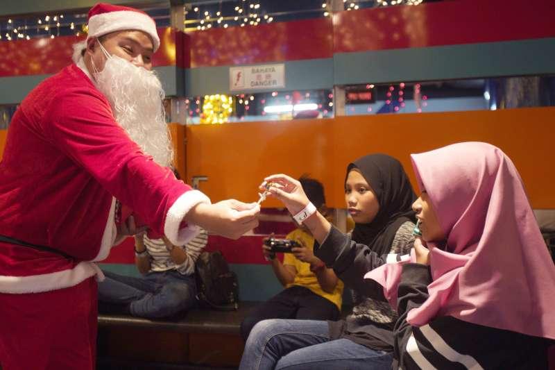 馬來西亞耶誕老人發糖果給女穆斯林(AP)