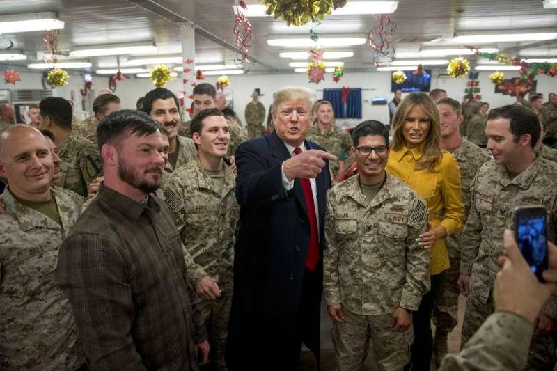 美國總統川普26日閃電訪問伊拉克,與約百名大多隸屬特種部隊的美軍寒暄,大玩自拍並替他們簽名。(AP)