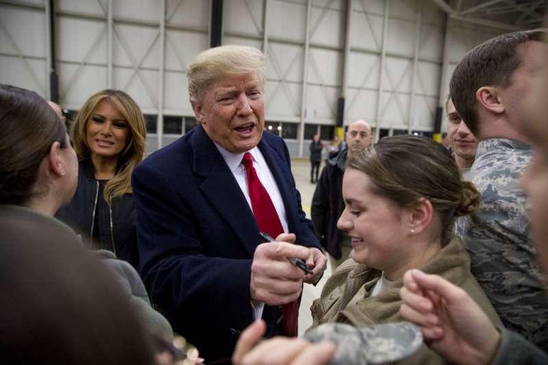 2018年12月26日,美國總統川普與第一夫人梅蘭妮亞造訪伊拉克美軍基地,為官兵簽名。(AP)