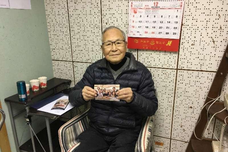97歲的香港老人勞永逸拿著與家人的合照。(新華社)